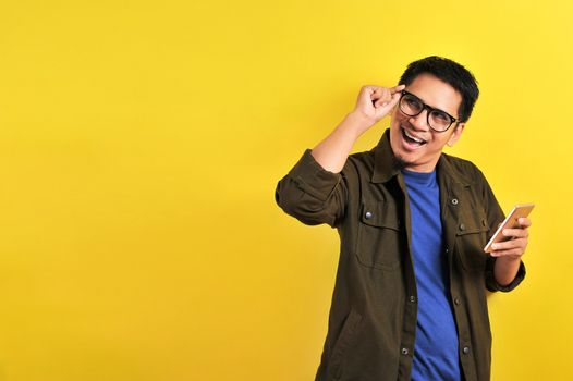 Portrait of happy smiling Asian man using smartphone wearing casual t-shirt and jacket with eyesglasses, get the best price, using simple mobile banking payment