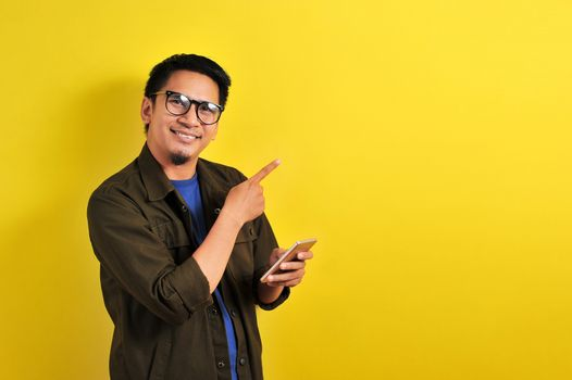 Portrait of happy smiling Asian man using smartphone pointing the copy space, get the best price, using simple mobile banking payment