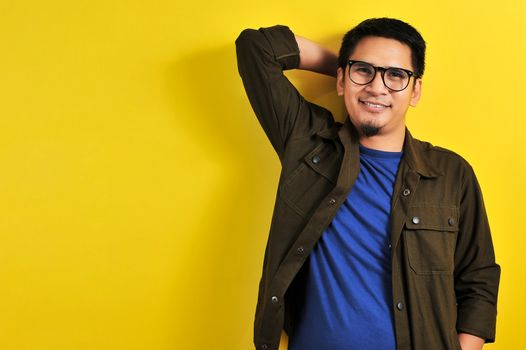 Portrait of a handsome man smile in blue t-shirt, jacket and eyesglasses, isolated on yellow background