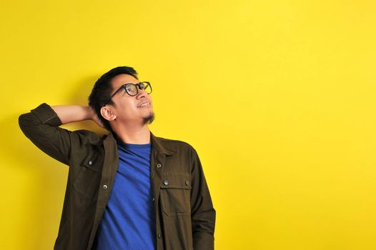 Asian man wearing glasses smiling look at copy space, isolated on yellow background
