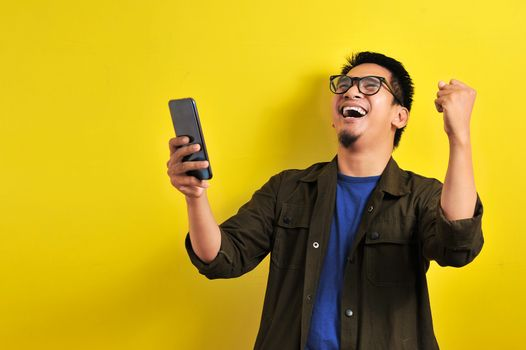 Asian man holding smartphone with winning gesture. Asian bussinesman winning gift or lottery, on yellow background