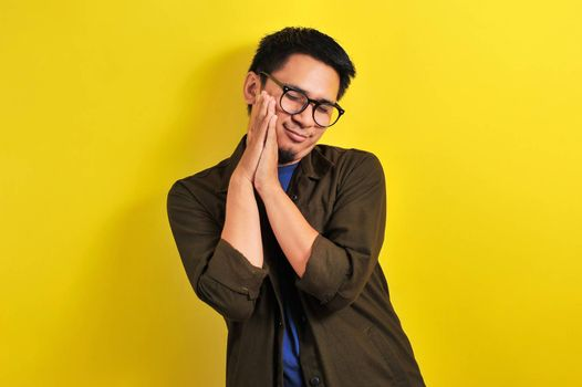 Asian man wear eyeglasses with sleep gesture, isolated on yellow