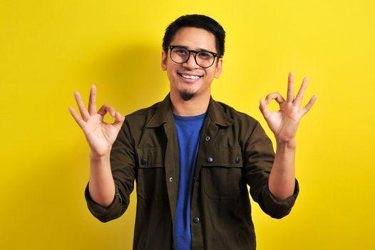 Indonesian man doing double okay wearing eyeglasses, Asian man smiling doing double okay gesture, isolated on yellow