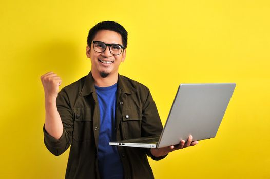 Asian man holding laptop with winning gesture. Asian bussinesman winning gift or lottery, on yellow background
