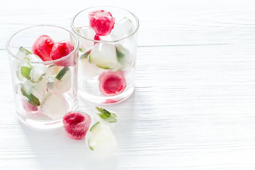 Cocktail glasses with berries in ice cubes on white table.