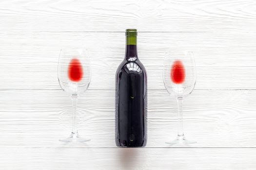 Wine bottle and glasses on white background from above
