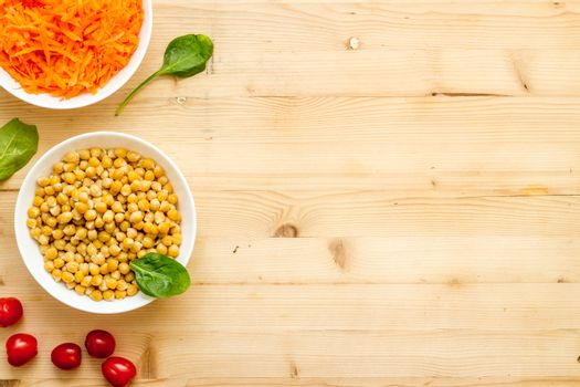 Vegetarian bowl with chickpeas and vegetables - wooden table top view copy space