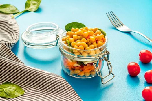 Vegan lunch. Chickpeas, carrot, tomato in glass jar on blue table