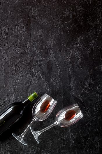 Wine bottle and glasses on black background from above copy space