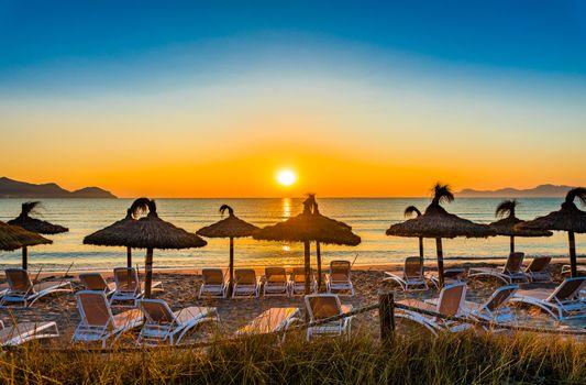 Beautiful sunset with orange sun over horizon on seaside beach