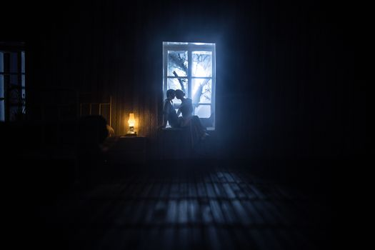 A realistic dollhouse bedroom with furniture and window at night. Romantic couple sitting on window. Man and woman making love in bedroom. Artwork table decoration . Selective focus.