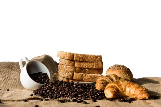 Bread and Croissant on the sackcloth with empty coffee cup and c