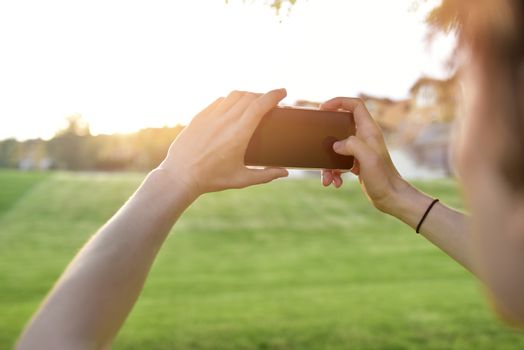 close-up guy takes pictures of nature, beautiful views on his smartphone. summer mood