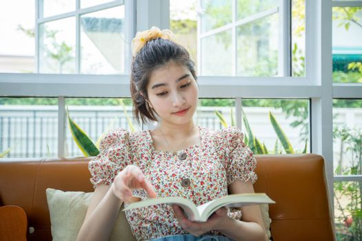 Asian women reading a book in the garden at home on a relaxing time