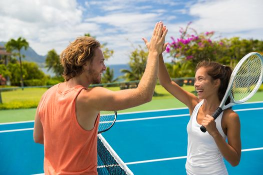 Fitness sport tennis couple giving high five energetic after fun mixed double game. Tennis players friends having fun doing fit sport at hotel ,summer travel vacation. Asian woman, Caucasian man.