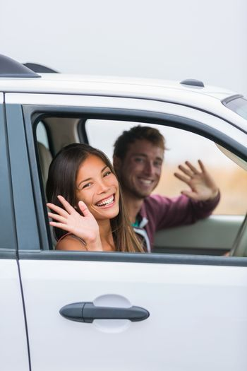 Happy multiracial couple leaving for road trip on summer vacation holiday. Young people driving car to travel destination waving goodbye.