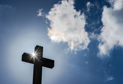 Cross against blue cloudy sky with sunbeams, religion christianity concepts background