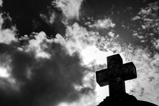 Black cross silhouette against cloudy sky, religion christianity concepts background