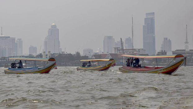 Thailand, Bangkok - March 2016: Long tailed taxi boats crossing the Chaophraya River on an overcast day