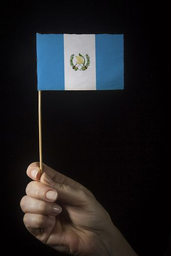 Hand with small flag of state of Guatemala