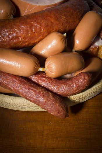 Set of various sausages in a wooden plate