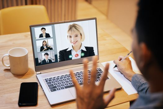young man working at home and using laptop computer with video conference