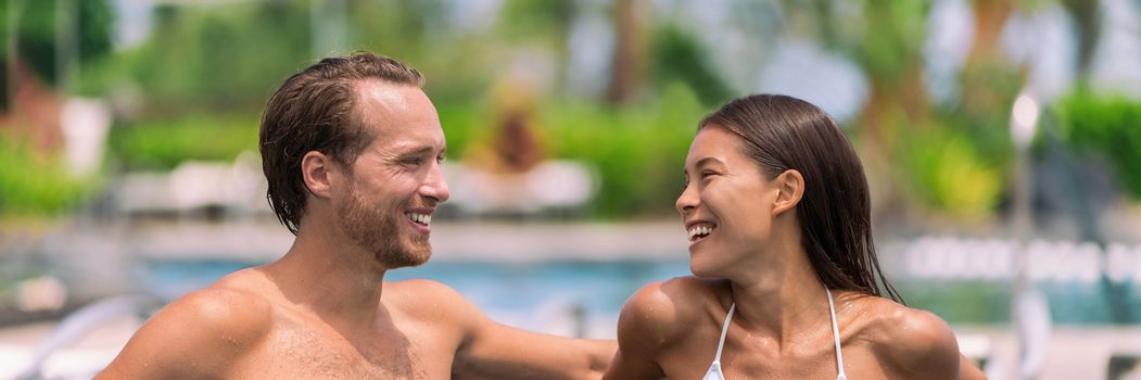 Happy couple having talking at luxury resort hotel travel beach holiday together on summer vacation. Asian woman, man relaxing by swimming pool.