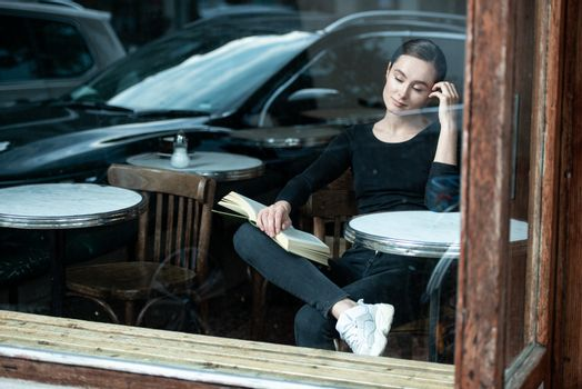 woman in coffee shop reading drinking cafe reading book in Paris
