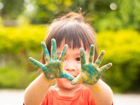 Cheerful little child girl with hands painted in colorful paints on nature background.