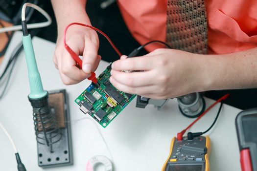 Hands of a man are engaged in the repair of electronics. Services, Manual assembly of the soldering circuit board.