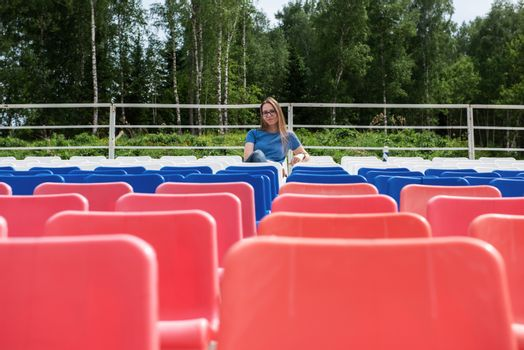 Lonely woman on the empty stadium outdoor. Empty tribune due to pandemic Covid-19. Concept of pandemic life , empty stadiums, distance from viewers, safety.