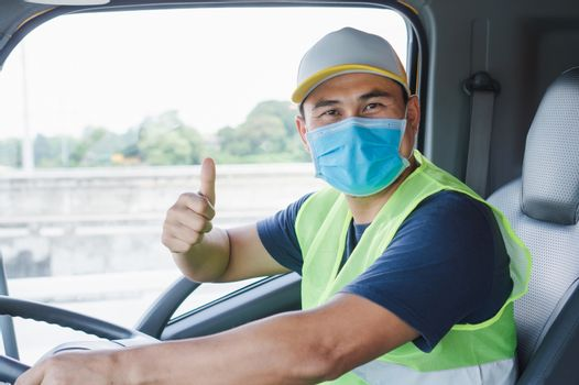Professional worker, truck driver, middle-aged Asian man wearing protective mask And safety vests For a long transportation business