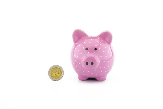 Cute pink piggy bank and euro coin on white with copyspace for financial or savings concepts