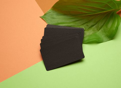 piles of black paper empty business cards on orange-green background, flat lay