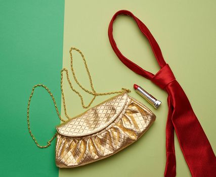 golden fashion handbag on a chain and a red silk tie on a green background, top view
