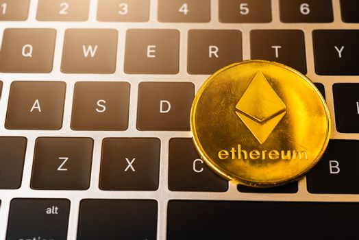 Golden ether coins or Ethereum network exchange on keyboard of laptop computer, electronic money world, blockchain and money cryptocurrency (crypto currency) concept