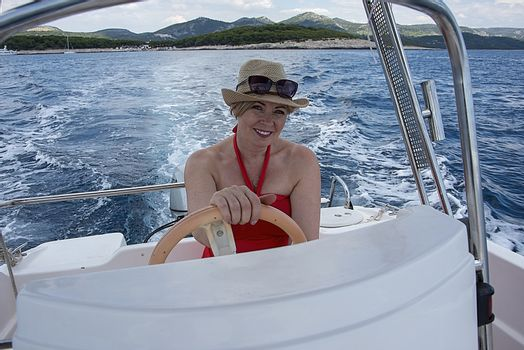 Croatia, Hvar - June 2018: Women in mid 40`s driving a small boat. She wears a straw hat and sunglassed perched on her head.