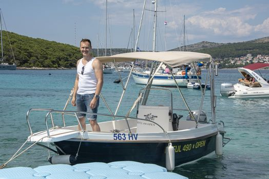 Croatia, Hvar - June 2018: Caucasian man, mid 40's , stands on the deck of a small boat