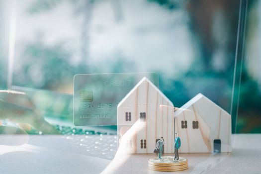 Business and financial concept. Double exposure hand holding credit card and wooden home with small people model stand on a stack of golden coins.