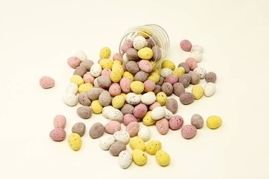 Small brightly coloured sugar coated chocolate Easter eggs spilling out from and supporting a shaped glass cup