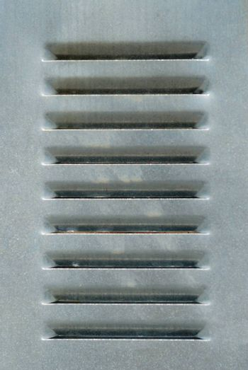 Gray metal aluminium grate with parallel vents.