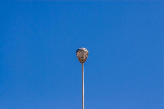 Single tall metallic street light against clear empty blue sky.