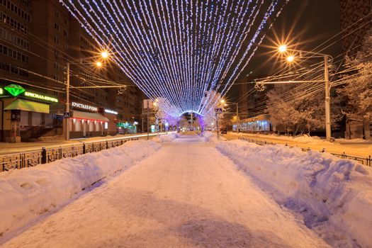 Walk of the city at night in winter. Alley with lights, trees, garlands covered with snow.
