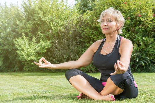 Attractive senior blond woman is sitting cross legged doing yoga in the garden.
