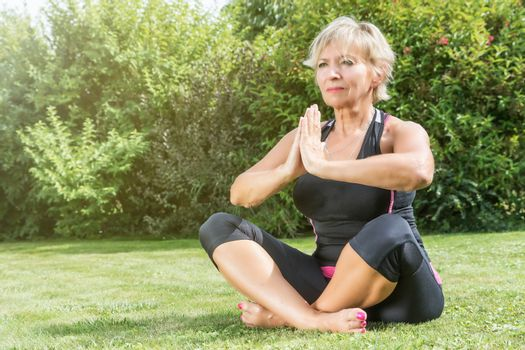 Attractive senior blond woman is sitting cross legged in a yoga position in the garden.