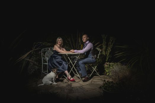Quorn, UK - Aug 2019: Couple holding hands on a garden bench at night, dog in forground