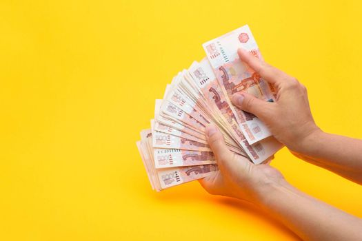 Hands count money in a bundle of notes, yellow background