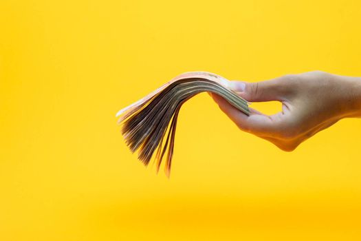 Hand holds out a wad of money, yellow background