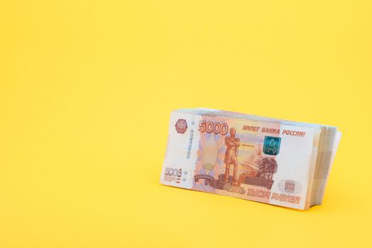 A pack of five thousandth bills on a yellow background