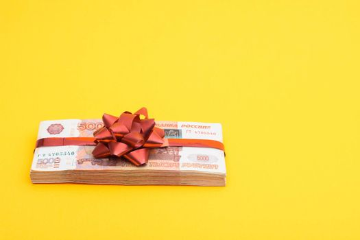 Gift pack tied with a red bow of five thousandth Russian bills on a yellow background